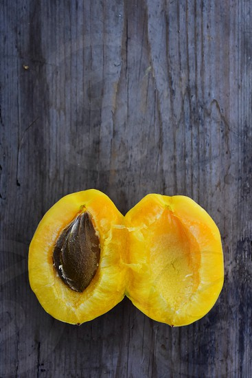yellow peach with black seed sliced into 2 halves on black wooden surface photo