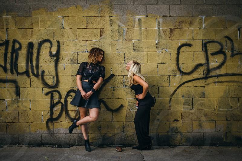 woman and woman laughing by a graffiti wall photo