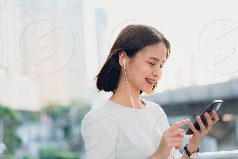 Women are listening to music from white headphones. And using hands touch to use various functions happy mood.  photo