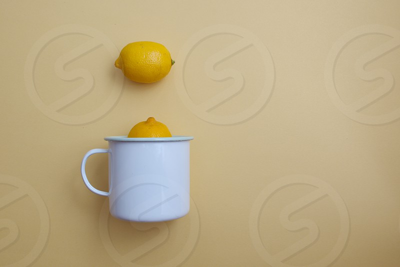 White enamel container and lemon against the yellow background photo