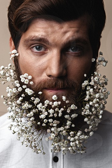 Creative Portrait of young beautiful man with a beard decorated with flowers. photo
