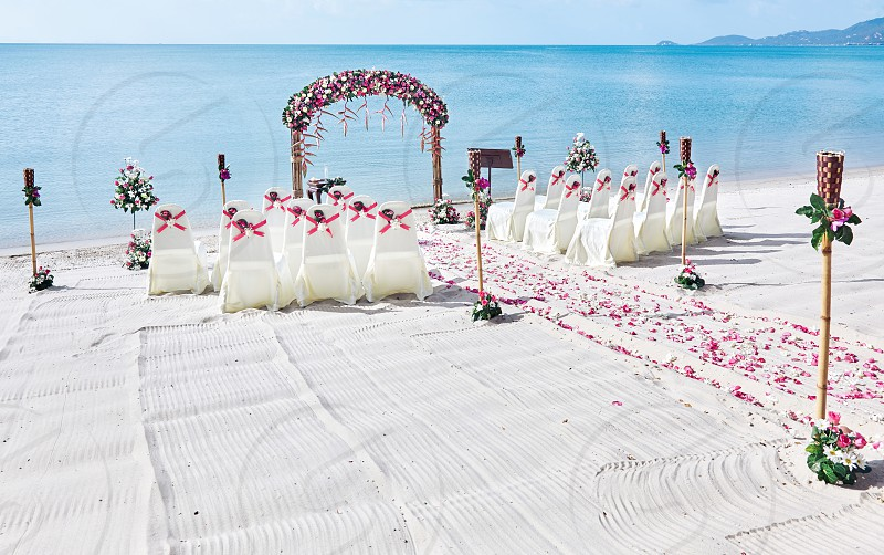Romantic beautiful colorful wedding venue on the beach setting with panoramic sea view background Pink and red roses petal on the aisle photo