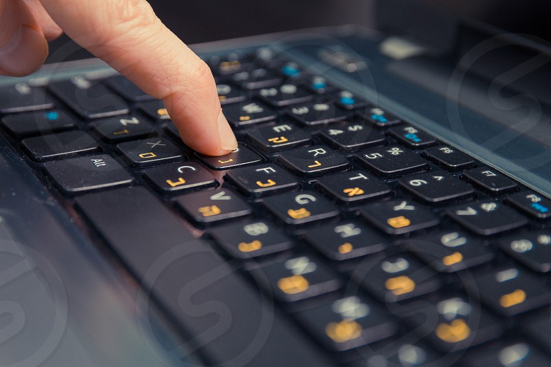Man typing on a keyboard with letters in Hebrew and English - Laptop keyboard - Close up photo