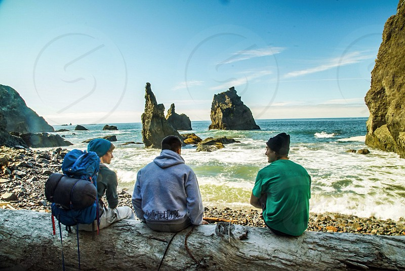 3 men sitting on brown log photo