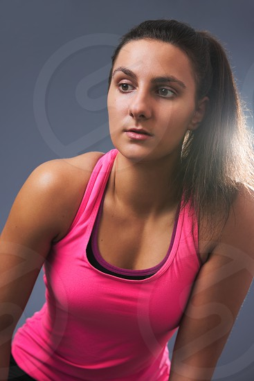 Young Beautiful Sporty Woman Leaning Forward on Gray Background photo