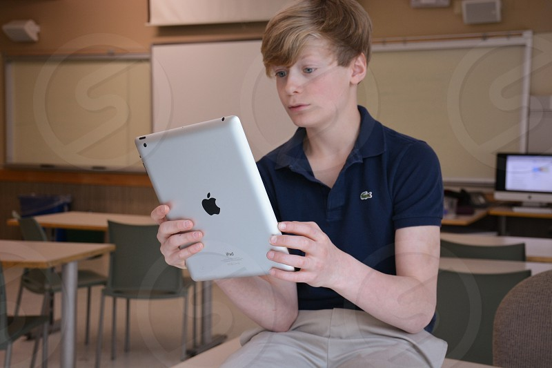 boy in black polo shirt and khaki pants holding an ipad photo