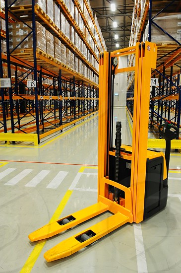 Yellow forklift in warehouse industrial storage racking in background industrial manufacturing transportation and logistics concept photo