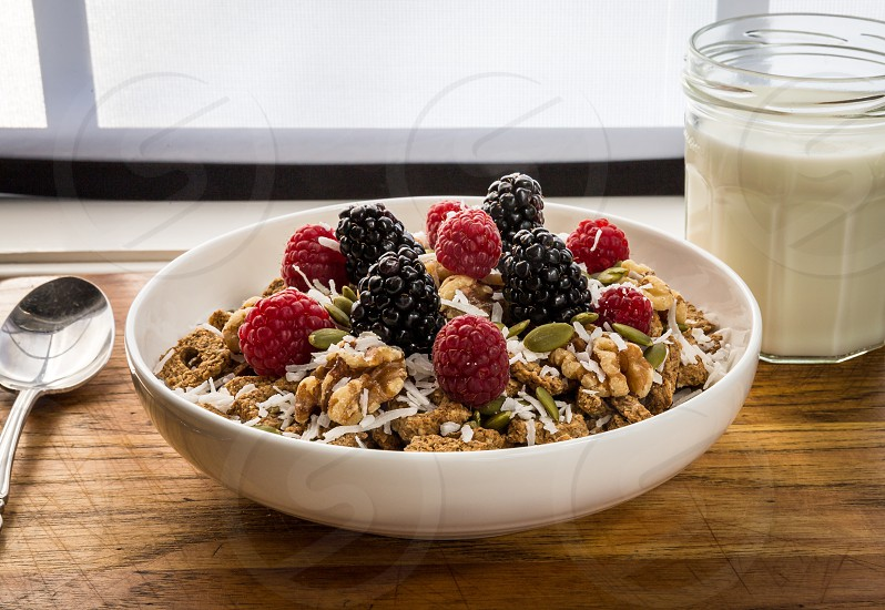 blackberry and raspberry on top of oatmeal beside glass milk on brown wooden table photo