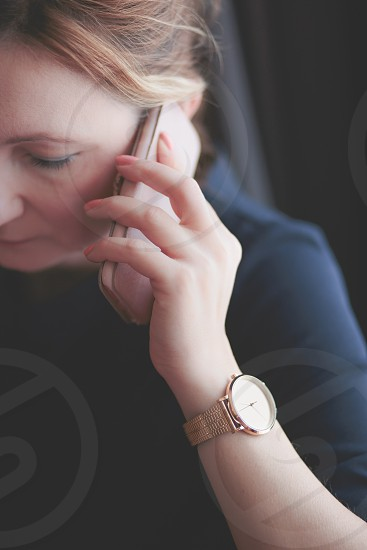 Elegant woman talking on mobile phone wearing pink gold wristwatch with bracelet and blue dress photo