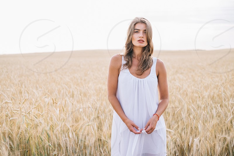 woman wearing white tank dress in the middle of wheat field during daytime photo
