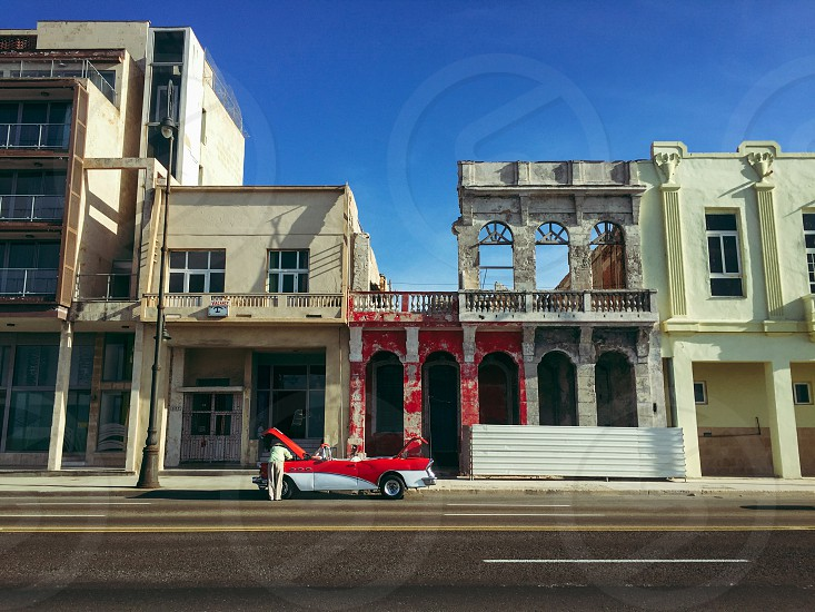 person checking on opened hood red and white convertible coupe outside red and beige concrete buildings photo