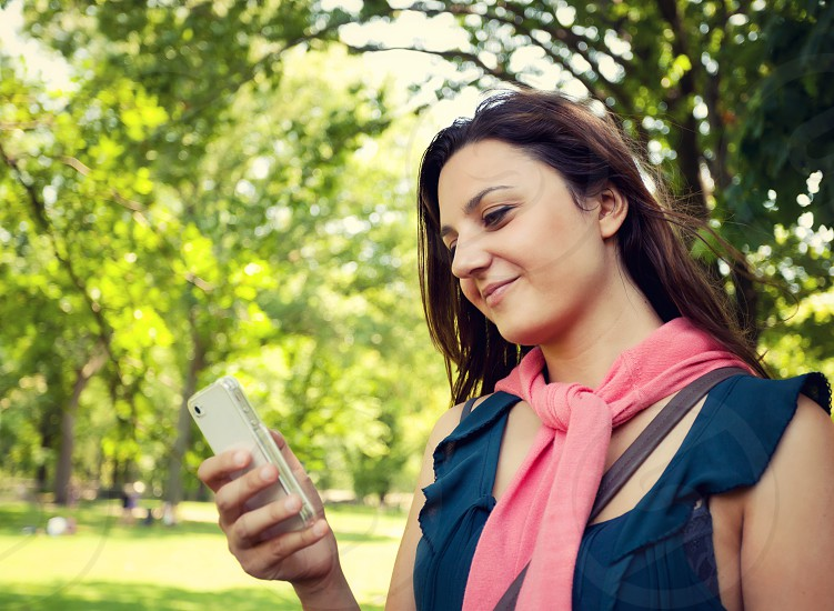 Young woman using smartphone in Central Park in New York City with coral sweater tied around his neck. photo