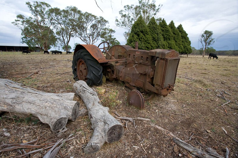 Derelict tractor or farm junk lying in a field on a farm photo