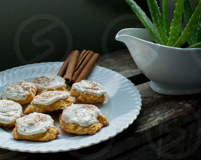 Cinnamon Pumpkin Cookies with Cinnamon sticks on White Plate near Succulent Plant.  photo