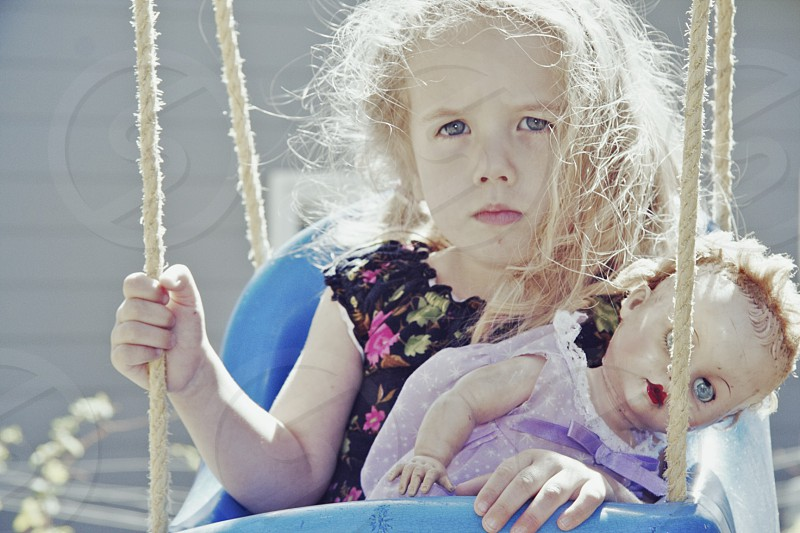 girl's and a doll at the swing photo