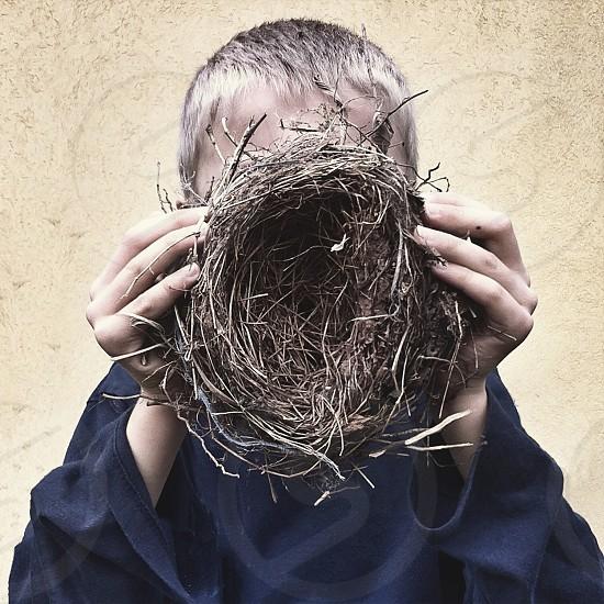 Boy hidden behind birds nest  photo