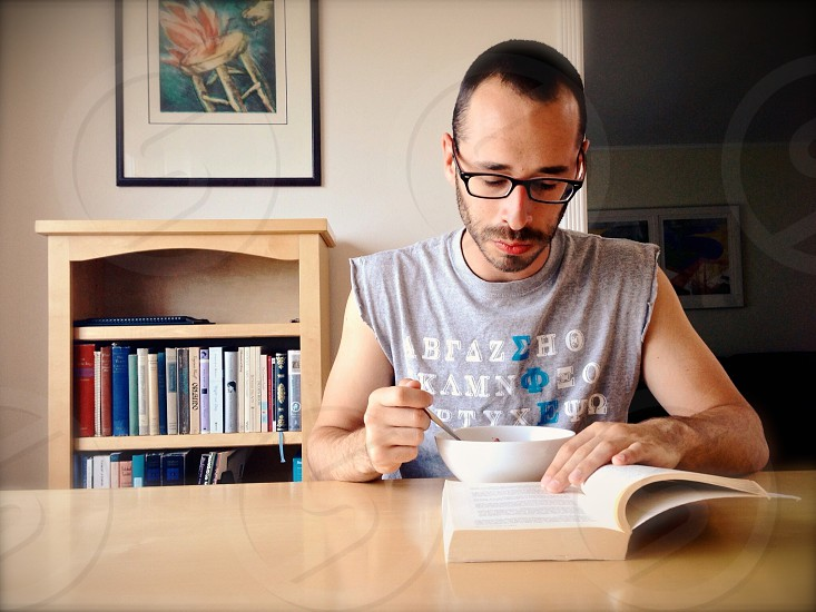 man sitting on chair near table eating and reading book photo
