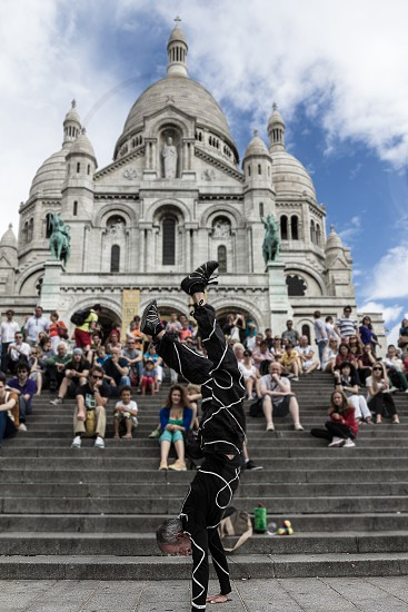 people watching man in black suit performing hand stand photo