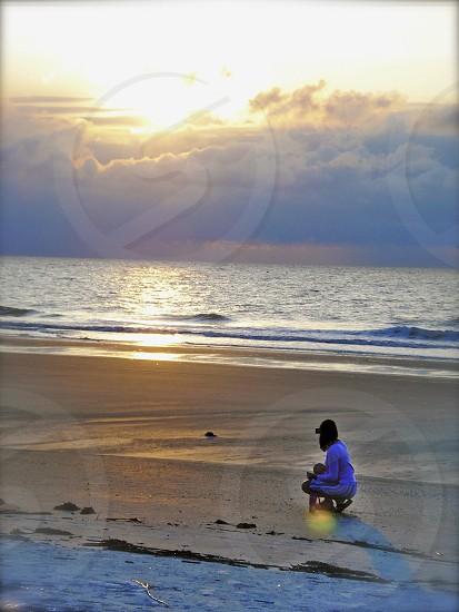 Woman looking for shells on the beach at sunrise. (original color) Hilton Head Island SC photo