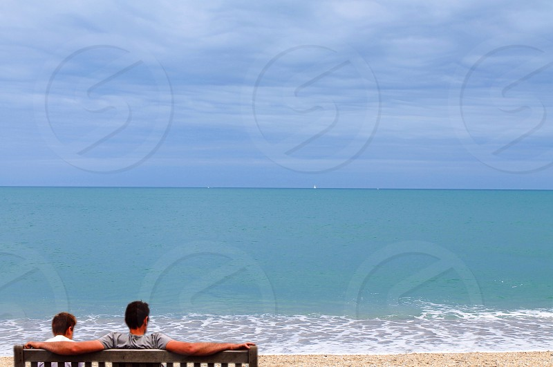 man in gray  crew neck t-shirt sitting on gray bench on the beach photo