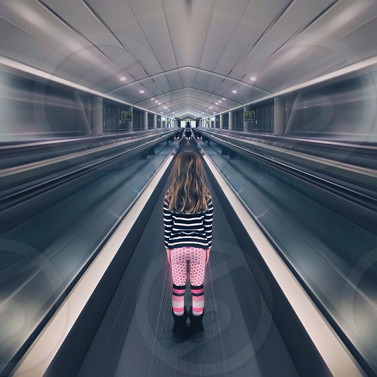 woman in black and white striped shirt standing on walkway in airport photo