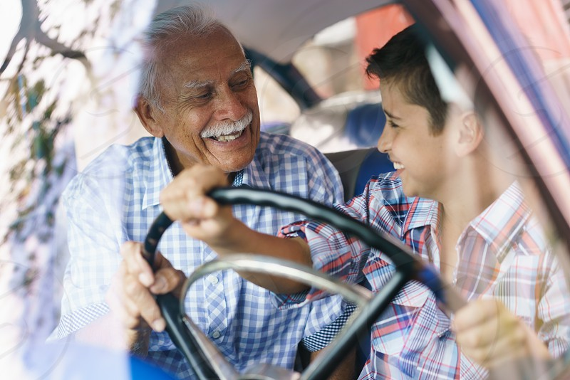 grandpa kid car drive class lesson driving american auto automobile boy cheerful child elderly enjoy excited family friendly generation gap grandchild grandfather grandparent grandson happy hispanic learning lifestyle man old passion people persons practice relationship retired retirement senior smiling steering wheel teaching together transportation vehicle vintage wheel young photo
