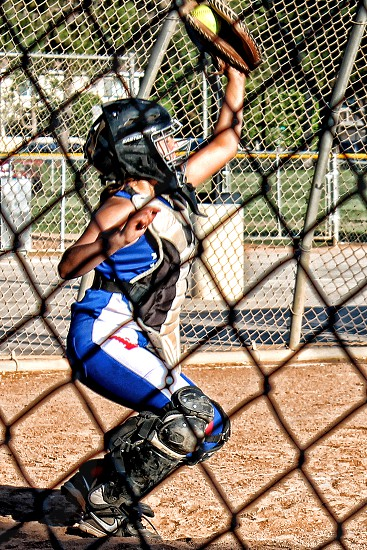 The softball catcher prevents a wild pitch by catching a ball that is high and away. photo