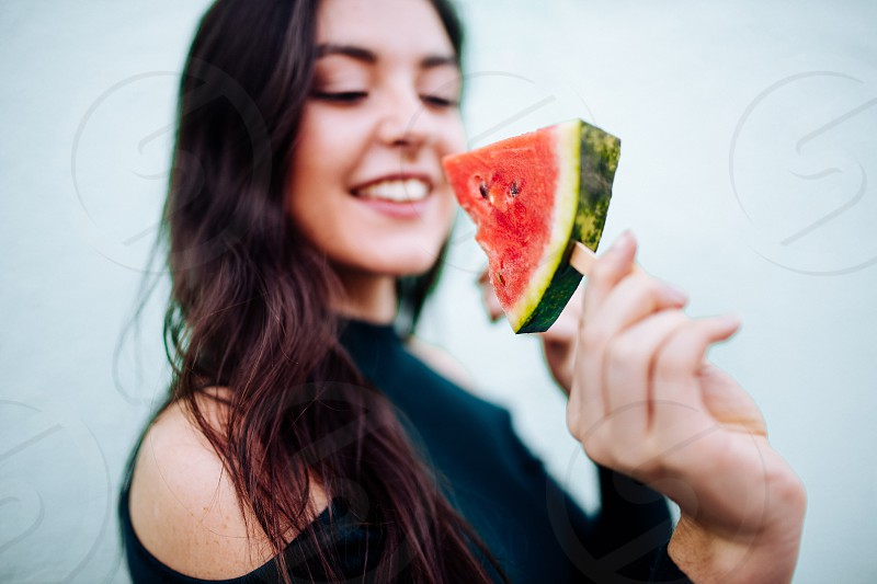 Young woman eating watermelon popsical photo