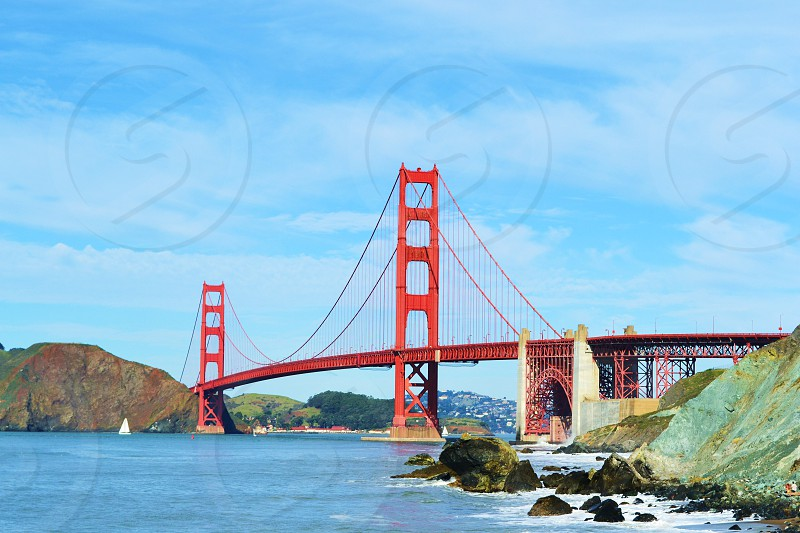 Long shot of Golden Gate Bridge with blue sky and rocks photo