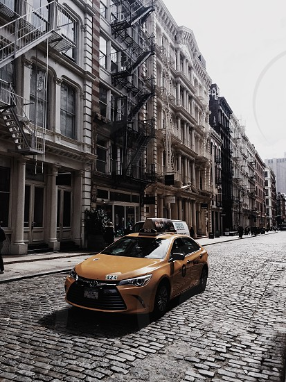 yellow taxi in road next to buildings photo