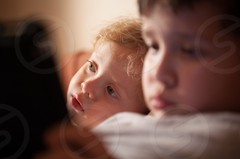 Cute young child with curly blond hair relaxing with his brother leaning his head on his shoulder and staring off into the distance photo