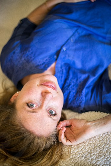 A young woman laying on the floor upside down with a slight smile while looking at the camera. Blouse hair pearl earrings Caucasian girl lady relaxed comfortable natural honest home blue carpet. photo