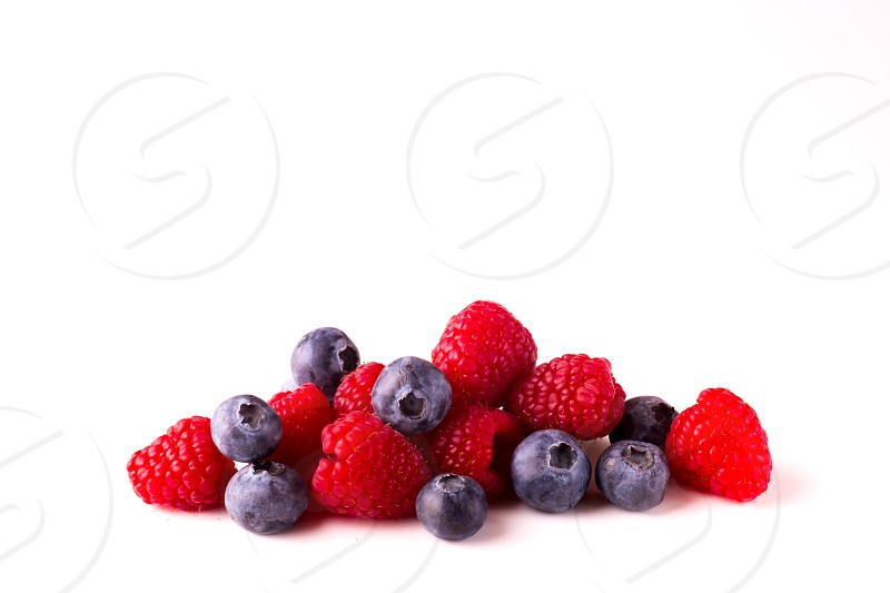 Blueberries and Raspberries on white background photo