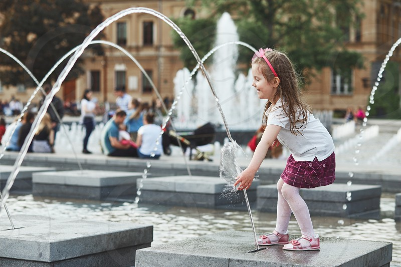 Little happy girl playing with the water in fountain in the center of town. Child catching a water stream going from a fountain. Candid people real moments authentic situations photo