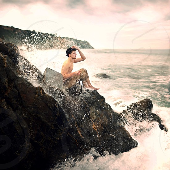 man in brown pants sitting on rock while holding a black cap beside a kerosene lamp while sea waves are hitting the rock photo