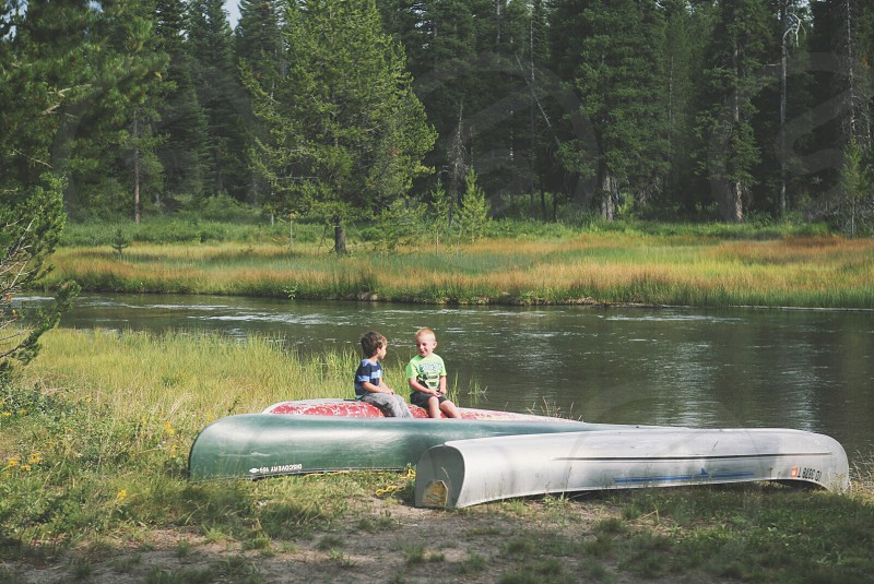 two boys sitting on an upside down canoe photo