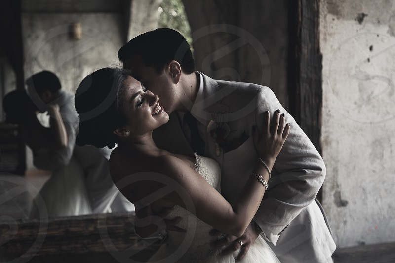 A newly wed couple holding and kissing one another in an old rustic building photo