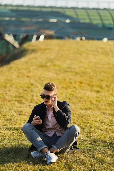 Yonug boy sitting on the grass wear glasses and text on his phone to friend photo