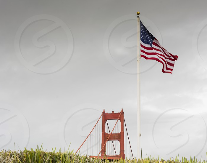 pillar of the Golden Gate Bridge with American flag and grass photo