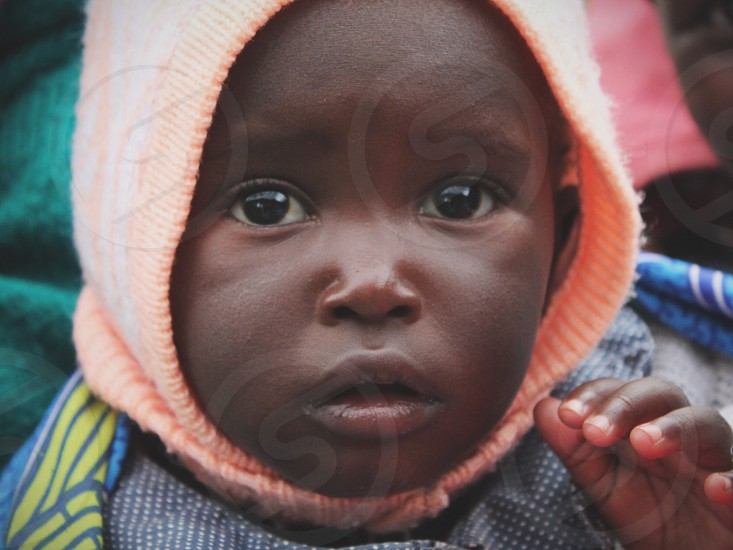 child with orange handkerchief on head photo