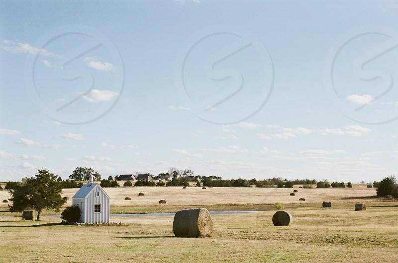 country peaceful farm farming white farmhouse hay hay bale blue golden field rural isolated Texas  photo