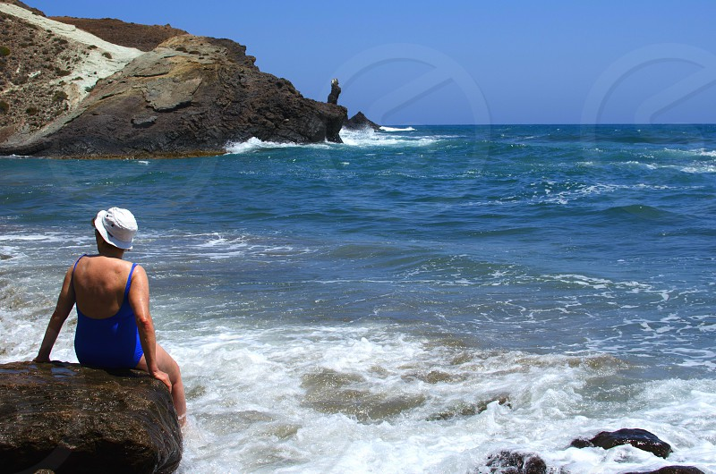 Elderly lady sitting on a rock with feet in the water and watching the Mediterranean sea in Cabo de Gata Andalusia Spain photo