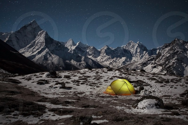 Camping in the himalayan mountains. Lonely tent lit up from inside in the valley under Ama Dablam mountain on a starry night. photo