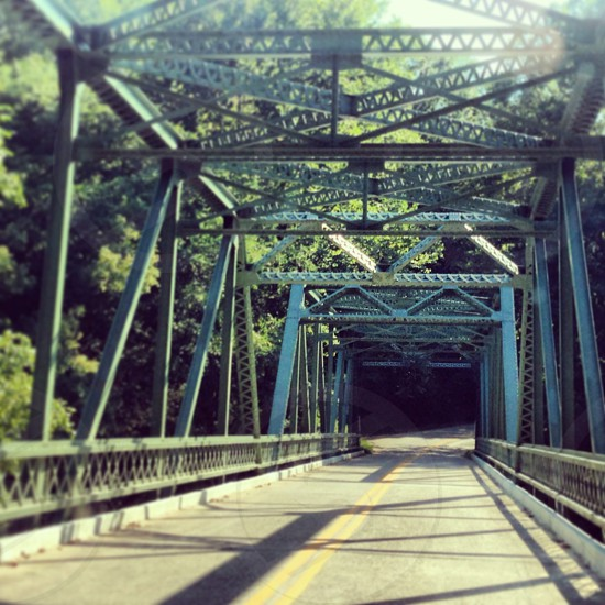 """Zoom"" A truss bridge stands strong in the daylight creating shadows. photo"