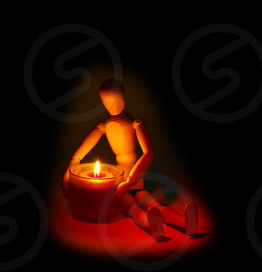 wood mannequin and candle glowing on the dark over black background photo