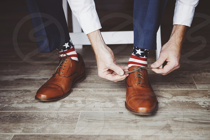 man tying his shoelace showing off his North American flag socks photo