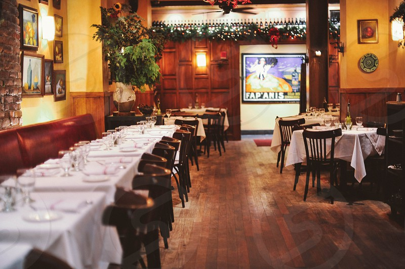 interior restaurant view with white linen table covers and wood chairs on hardwood floors photo