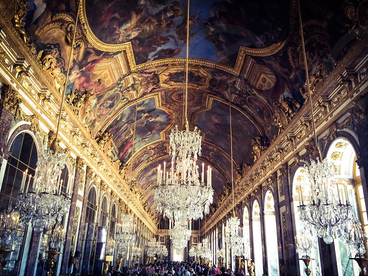 glass chandeliers hanging from cathedral ceiling with paintings photo