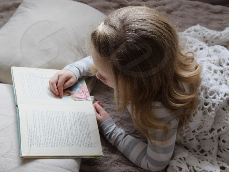 girl wearing gray and white sweater laying down in bed while reading book photo
