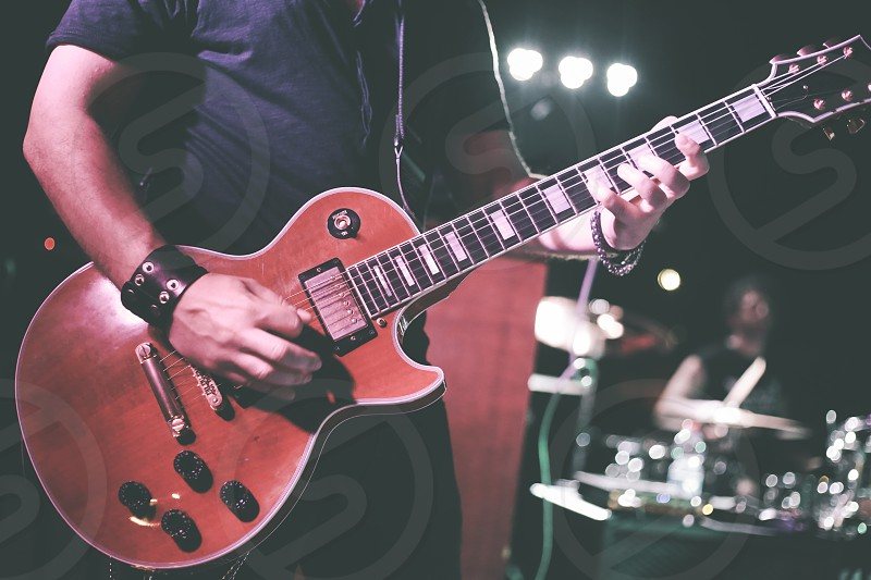 A musician plays the electric guitar during a live concert photo